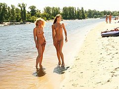 Blonde nudist kicks up some water at a nude beach